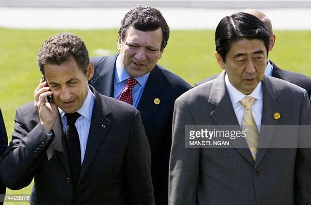 French President Nicolas Sarkozy talks on his phone while walking with Japanese Prime Minister Shinzo Abe and European Commission President Jose...