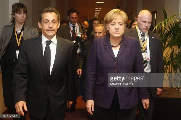 French President Nicolas Sarkozy walks with German Chancellor Angela Merkel prior to an extraordinary European Union summit at the European Council...