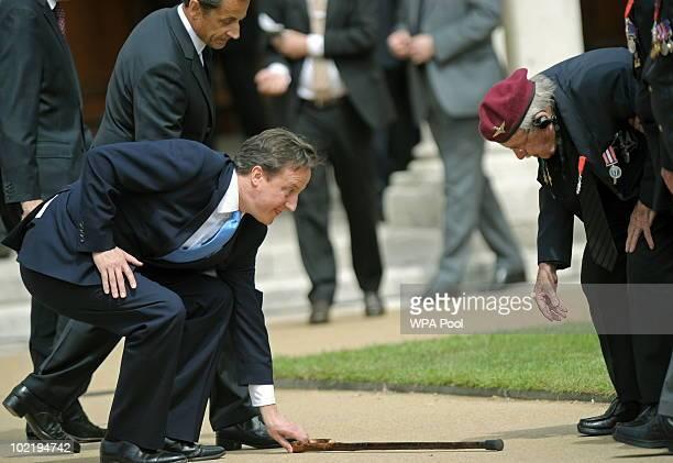 French President Nicolas Sarkozy watches as British Prime Minister David Cameron picks up the walking stick of World War II veteran and Legion de...