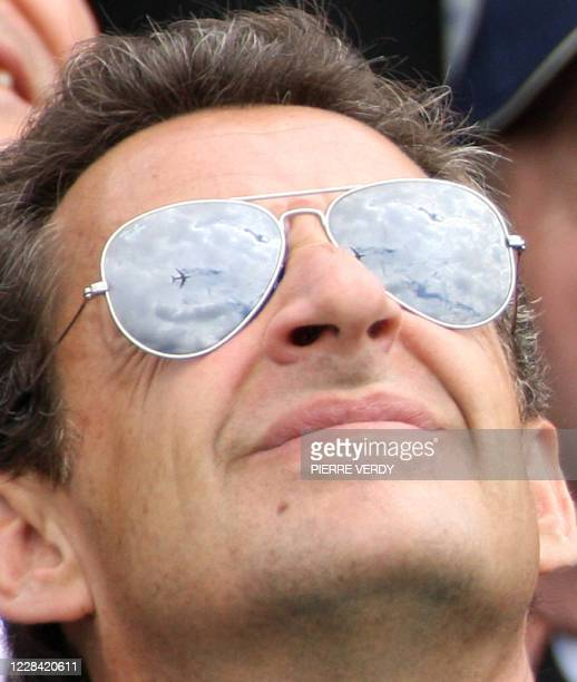 French President Nicolas Sarkozy watches the flying displays while visiting the 47th International Paris Air Show at Le Bourget Airport 23 June 2007....