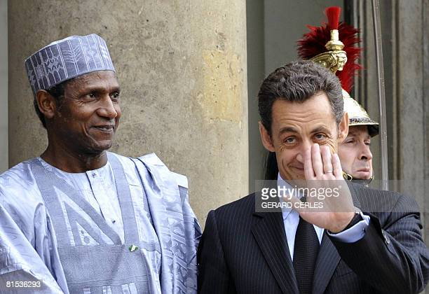 French President Nicolas Sarkozy waves flanked by his Nigerian counterpart Umaru Yar'dua prior to an official lunch on June 12 2008 at the Elysee...