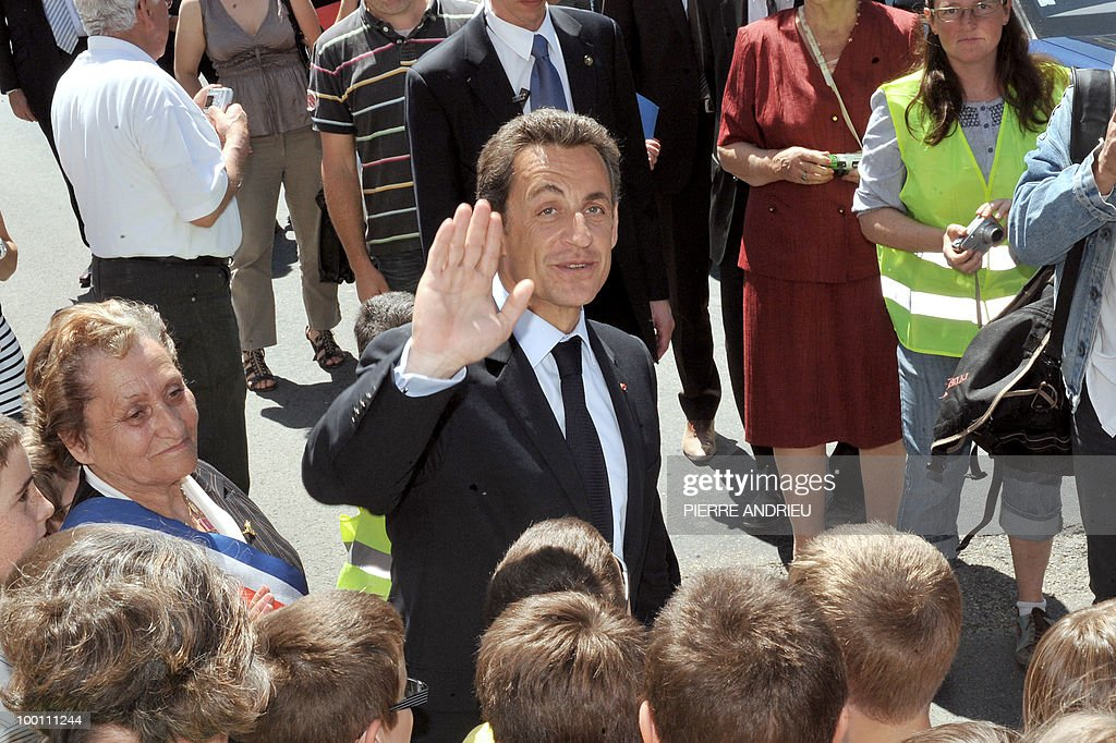 French President Nicolas Sarkozy (C) waves to the crowd after visiting a local farm, on May 21, 2010 in Bouglon, southwestern France, during his visit in the region.