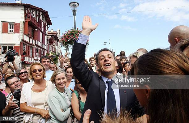 French president Nicolas Sarkozy waves to the crowd before having lunch in the French Basque city of Ciboure southwestern France 24 August 2007 The...