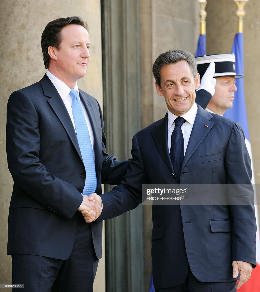 French President Nicolas Sarkozy (R) welcomes the new Britain's Prime minister David Cameron at the Elysee Palace on May 20, 2010 in Paris. Cameron and his coalition deputy unveiled full details today of their 'historic' power-sharing deal, under growing scrutiny for signs of strain.