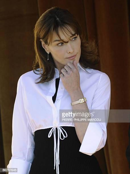 French President Nicolas Sarkozy's wife Carla BruniSarkozy reviews the honor guard at the El Pardo Palace in Madrid on April 27 2009 Sarkozy who pays...