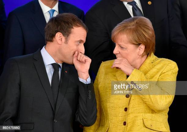 TOPSHOT French President of Republic Emmanuel Macron talks with German Chancellor Angela Merkel during the family photo after the Reinforcing...