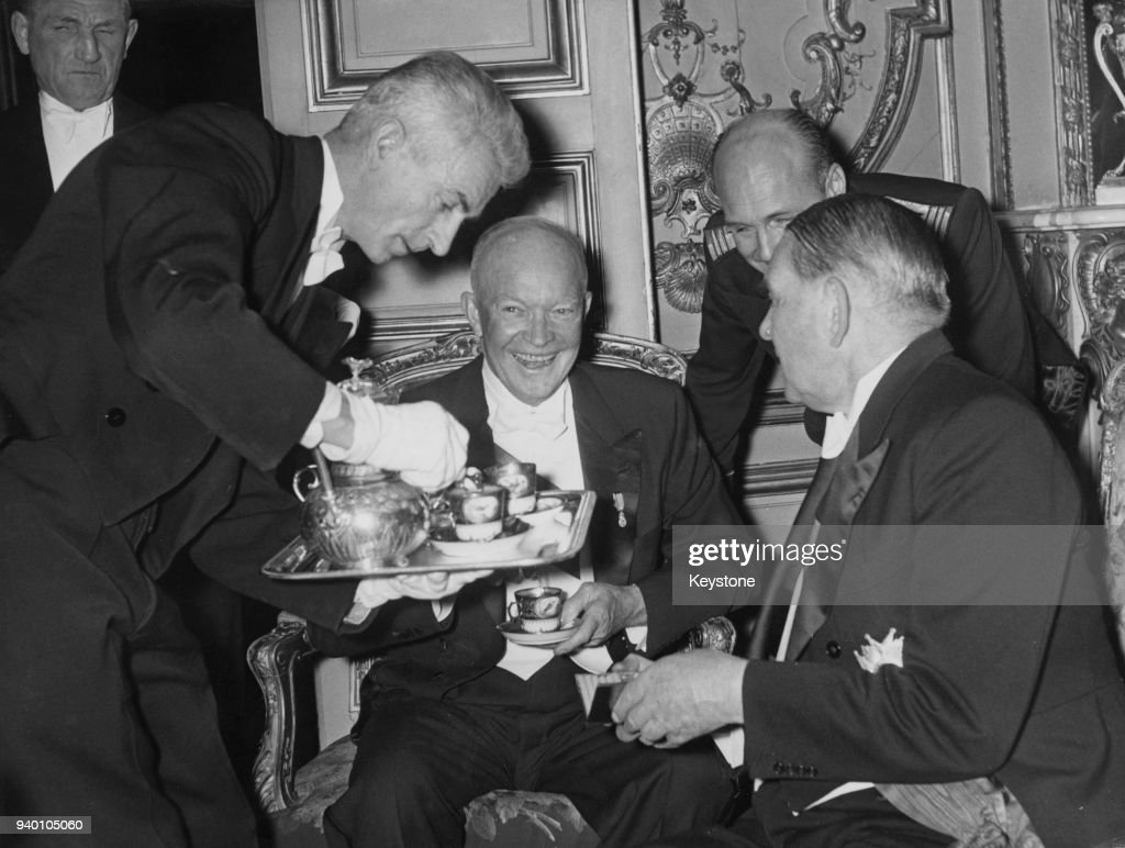 French President René Coty (1884 - 1962, right) takes coffee with US President Dwight D. Eisenhower (1890 - 1969, centre) at the Elysée Palace in Paris, France, after throwing a State Banquet for the NATO heads of government, 18th December 1957.