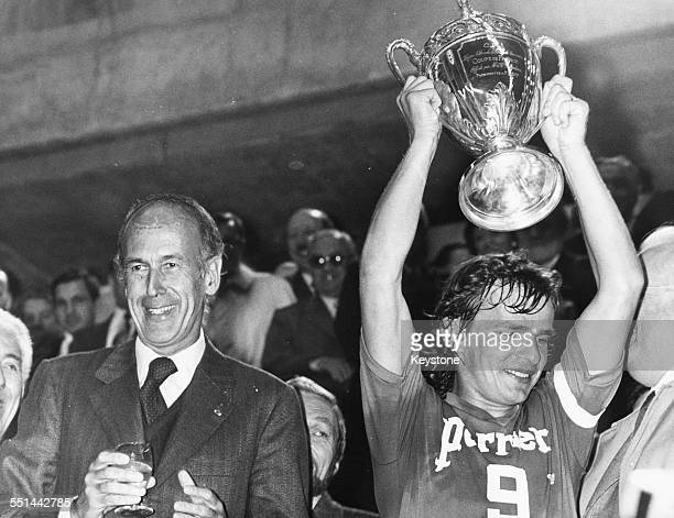 French President Valery Giscard D'Estaing celebrating with football player Georges Bereta, captain of Saint Etienne Football Club, holding the Coupe...