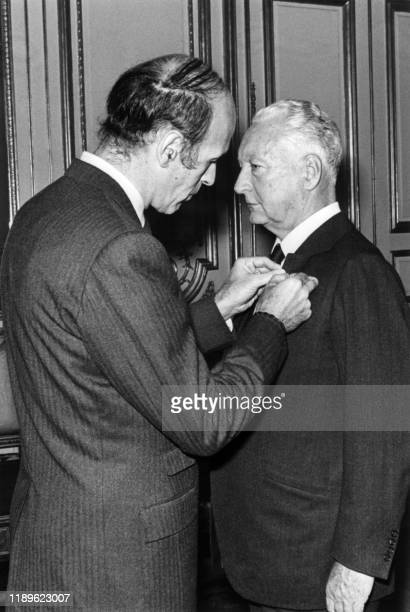 French President Valéry Giscard d'Estaing presents the insignia of the Grand Officer of the Legion of Honor in a military capacity to Pierre Messmer...