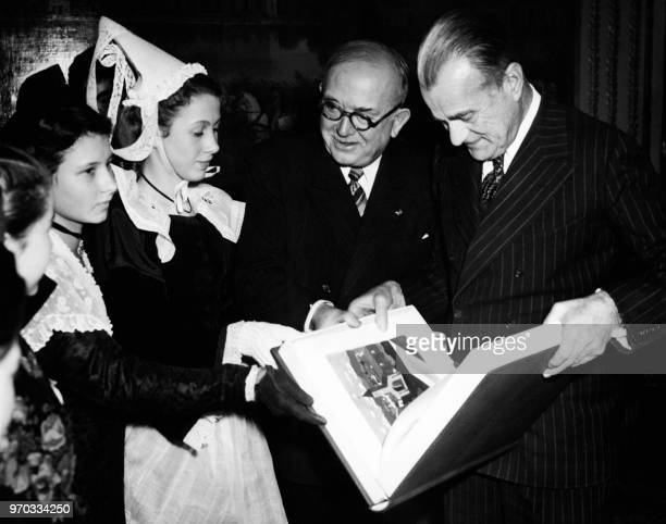 French president Vincent Auriol and United States Ambassador to France Jefferson Caffery examine a thankyou book to the American children from French...