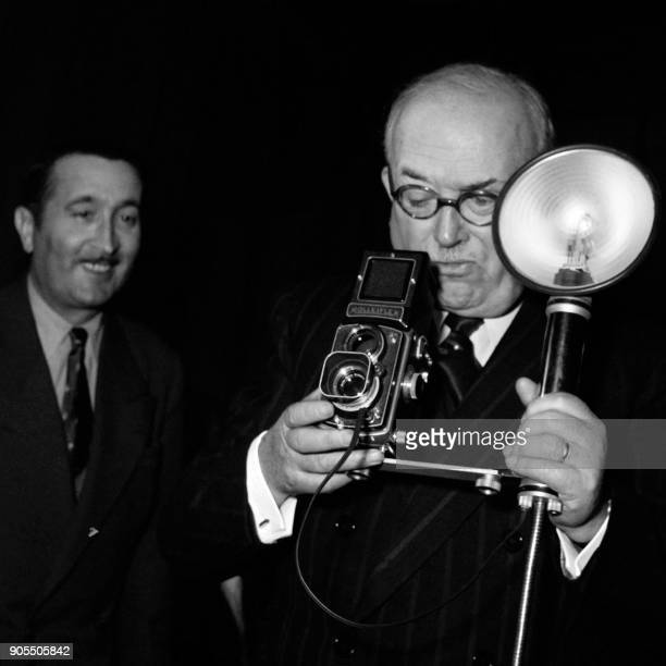 French president Vincent Auriol takes a picture on January 9 1954 as photographers offer him a photo album of the ministry buildings under his...