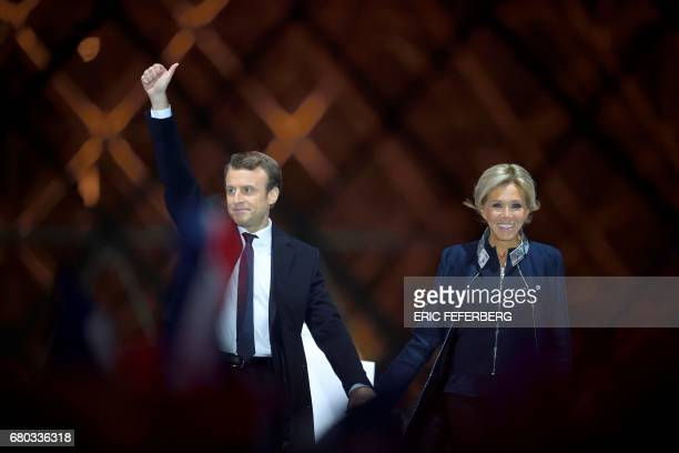French presidentelect Emmanuel Macron and his wife Brigitte Trogneux greet supporters in front of the Pyramid at the Louvre Museum in Paris on May 7...
