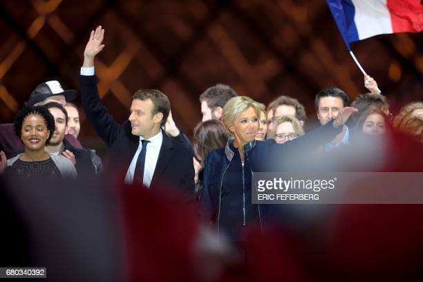 French president-elect Emmanuel Macron and his wife Brigitte Trogneux sing the national anthem with supporters in front of the Pyramid at the Louvre...