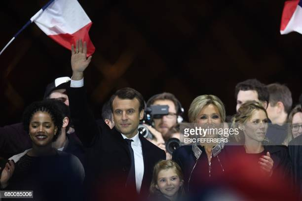 French presidentelect Emmanuel Macron his wife Brigitte Trogneux and his stepdaughter Tiphaine Auziere and granddaughter Emma greet supporters in...