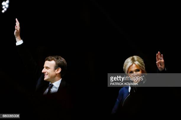 TOPSHOT French presidentelect Emmanuel Macron waves to the crowd next to his wife Brigitte Trogneux in front of the Pyramid at the Louvre Museum in...