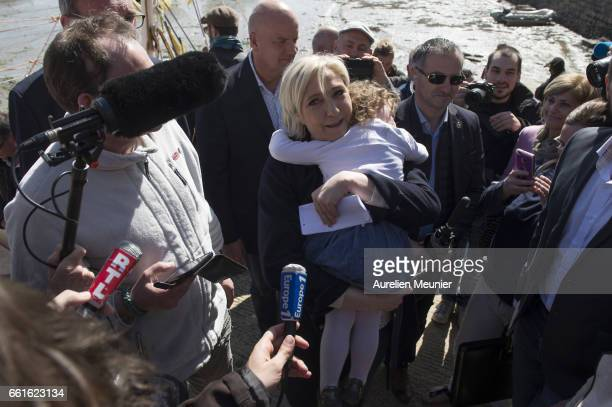 French Presidential candidate and Leader of the National Front Marine Le Pen hugs a child as she meets with professional fishermen on March 31 2017...