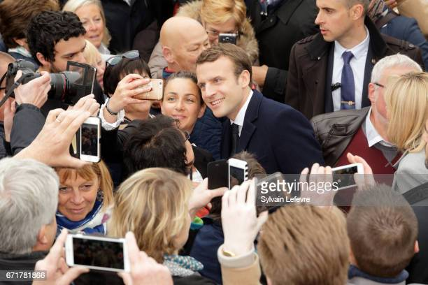 French presidential candidate Emmanuel Macron for the En Marche ! movement poses with supporters as he leaves the Touquet polling station after...