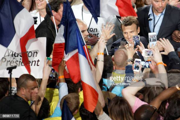 French presidential candidate Emmanuel Macron waves as he arrives to delivers a speech during a campaign rally at Bercy Arena on April 17 2017 in...