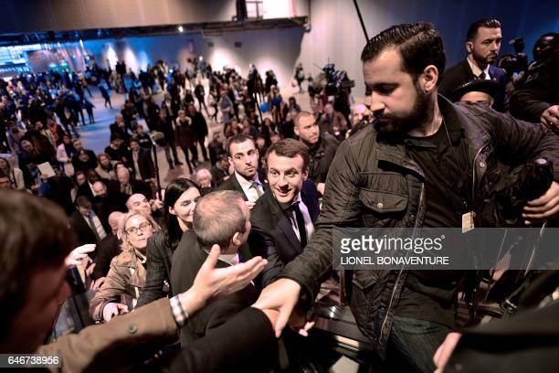 French presidential election candidate for the En Marche movement Emmanuel Macron shakes hands as he visits Paris' international agriculture fair on...