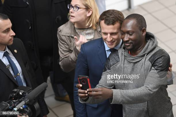 French presidential election candidate for the En Marche movement Emmanuel Macron takes a selfie with an employee during a visit to the APF...