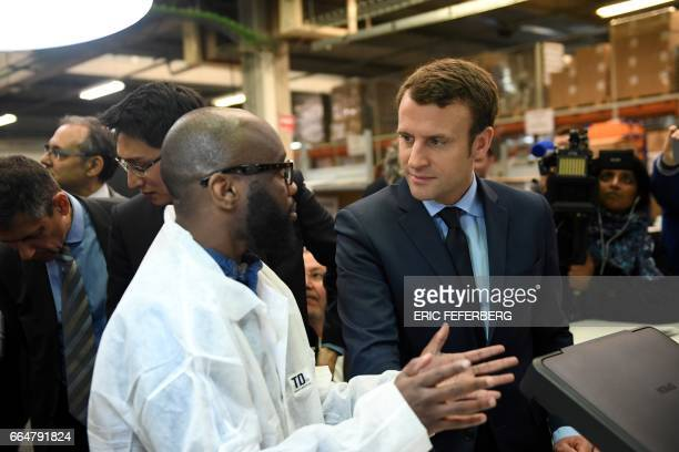French presidential election candidate for the En Marche movement Emmanuel Macron speaks with an employee during a visit to the APF Entreprise 93 a...