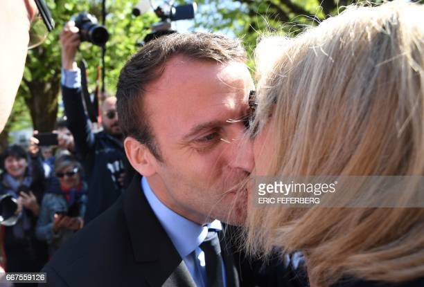 French presidential election candidate for the En Marche movement Emmanuel Macron kisses his wife Brigitte Trogneux during a campaign visit in...