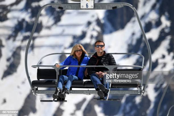 French presidential election candidate for the En Marche movement Emmanuel Macron and his wife Brigitte Trogneux sit on a chairlift on their way to...