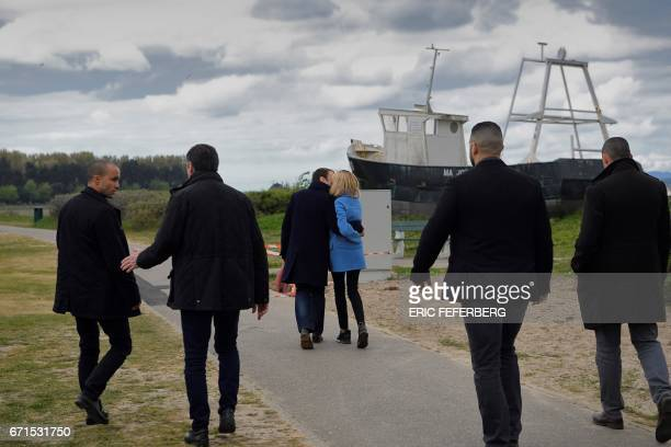 French presidential election candidate for the En Marche movement Emmanuel Macron and his wife Brigitte Trogneux surrounded by bodyguards kiss as...