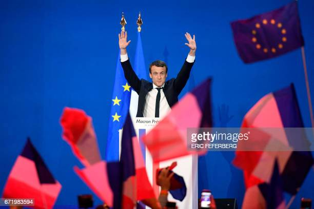 TOPSHOT French presidential election candidate for the En Marche movement Emmanuel Macron raises his hands as he arrives on stage to deliver a speech...