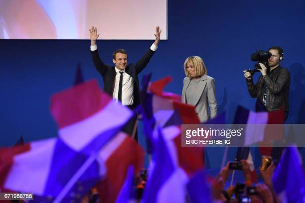 French presidential election candidate for the En Marche movement Emmanuel Macron and his wife Brigitte Trogneux arrive on stage at the Parc des...