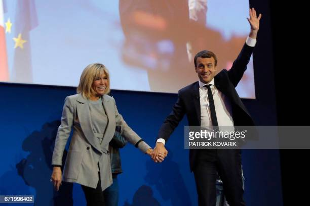 French presidential election candidate for the En Marche movement Emmanuel Macron and his Brigitte Trogneux react during a meeting at the Parc des...