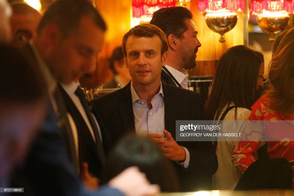 French presidential election candidate for the En Marche ! movement Emmanuel Macron (C) looks on at La Rotonde restaurant in Paris, on April 23, 2017, after the first round of the Presidential election. Pro-European Emmanuel Macron is set to face far-right candidate Marine Le Pen in France's presidential run-off, results showed on April 24, making him clear favourite to emerge as the country's youngest leader in its history. /