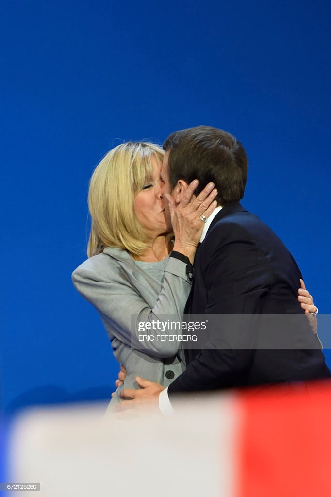 French presidential election candidate for the En Marche ! movement, Emmanuel Macron (R) kisses his wife Brigitte Trogneux on stage at the Parc des Expositions in Paris, on April 23, 2017, after the first round of the Presidential election. Pro-European Emmanuel Macron is set to face far-right candidate Marine Le Pen in France's presidential run-off, results showed on April 24, making him clear favourite to emerge as the country's youngest leader in its history. / AFP PHOTO / Eric FEFERBERG / ALTERNATIVE
