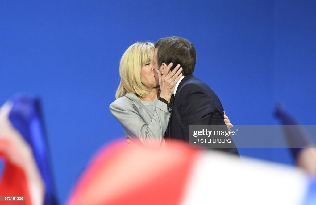 French presidential election candidate for the En Marche ! movement Emmanuel Macron kisses his wife Brigitte Trogneux (L) on stage at the Parc des Expositions in Paris, on April 23, 2017, after the first round of the Presidential election. /