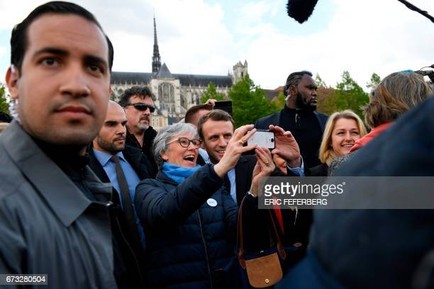 French presidential election candidate for the En Marche movement Emmanuel Macron poses for a 'selfie' with a supporter outside the Amiens Cathedral...
