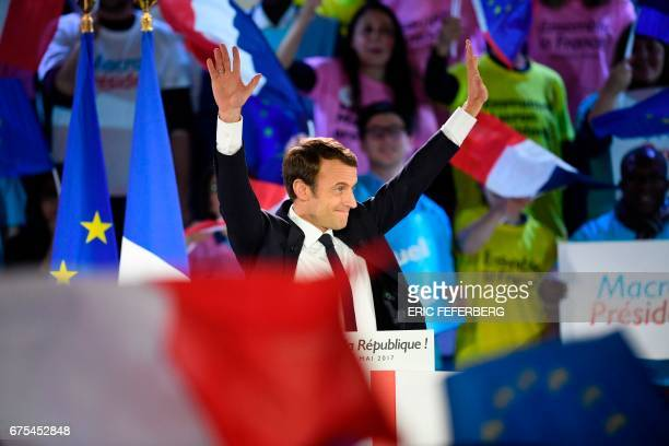 French presidential election candidate for the En Marche movement Emmanuel Macron waves upon his arrival on stage during a campaign rally on May 1...