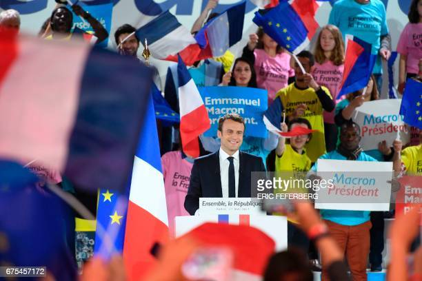 French presidential election candidate for the En Marche movement Emmanuel Macron acknowledges applause upon his arrival on stage during a campaign...