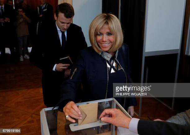 French presidential election candidate for the En Marche movement Emmanuel Macron waits as his wife Brigitte Trogneux casts her ballot at a polling...
