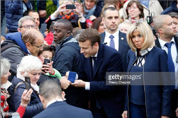 French presidential election candidate for the 'En Marche' political movement Emmanuel Macron and his wife Brigitte Trogneux leave the polling...