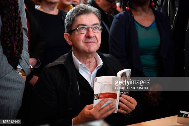 French presidential election candidate for the farleft coalition 'La France insoumise' JeanLuc Melenchon holds a copy of his book 'Le choix de...