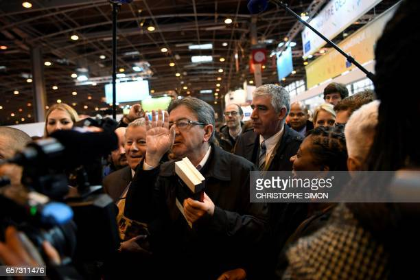 French presidential election candidate for the farleft coalition 'La France insoumise' JeanLuc Melenchon gestures as he holds copies of his book 'Le...