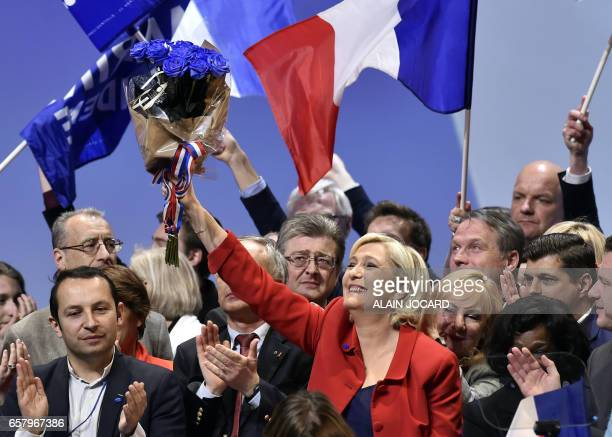 French presidential election candidate for the farright Front National party Marine Le Pen brandishes blue roses after speaking during a campaign...