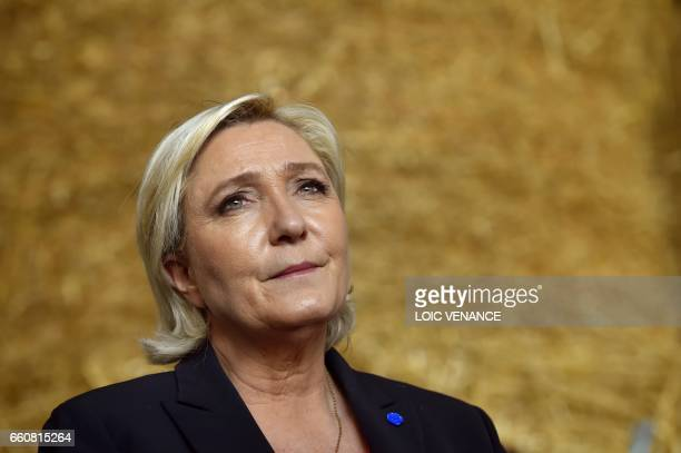 French presidential election candidate for the far-right Front National party Marine Le Pen looks on as she visits a pig farm while campaigning, on...