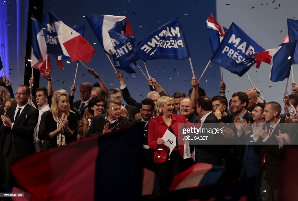French presidential election candidate for the far-right Front National (FN) party, Marine Le Pen (In Red) smiles after being handed a piece of paper marked 50% by FN vice-president in the regional council of the Ile-de-France region, Jean Lin Lacapelle,as FN member of parliament Gilbert Collard (3-L), FN party MP Marion Marechal Le Pen (2-L)and Mayor of Henin-Beaumont Steeve Briois (L) applaud during a campaign meeting in Paris on April 17, 2017. / AFP PHOTO / joel SAGET