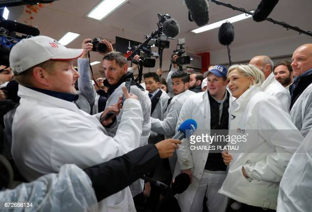 French presidential election candidate for the farright Front National party Marine Le Pen speaks to journalists as she visits the meat pavilion at...