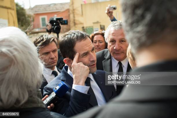 French presidential election candidate for the leftwing French Socialist party Benoit Hamon gestures as he speaks to journalists next to MP Henri...