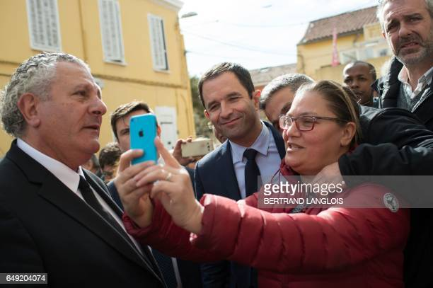 French presidential election candidate for the leftwing French Socialist party Benoit Hamon gestures flanked by MP Henri Jibrayel poses for a...