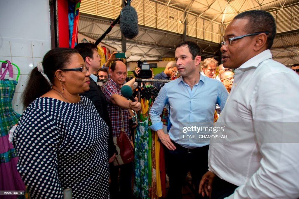 French presidential election candidate for the left-wing Socialist Party (PS) Benoit Hamon (C), flanked by Mayor of Fort-France Didier Laguerre, speaks to a vendor at the market of Fort-de-France on March 13, 2017, during a trip to the French overseas territory of Martinique. / AFP PHOTO / Lionel CHAMOISEAU