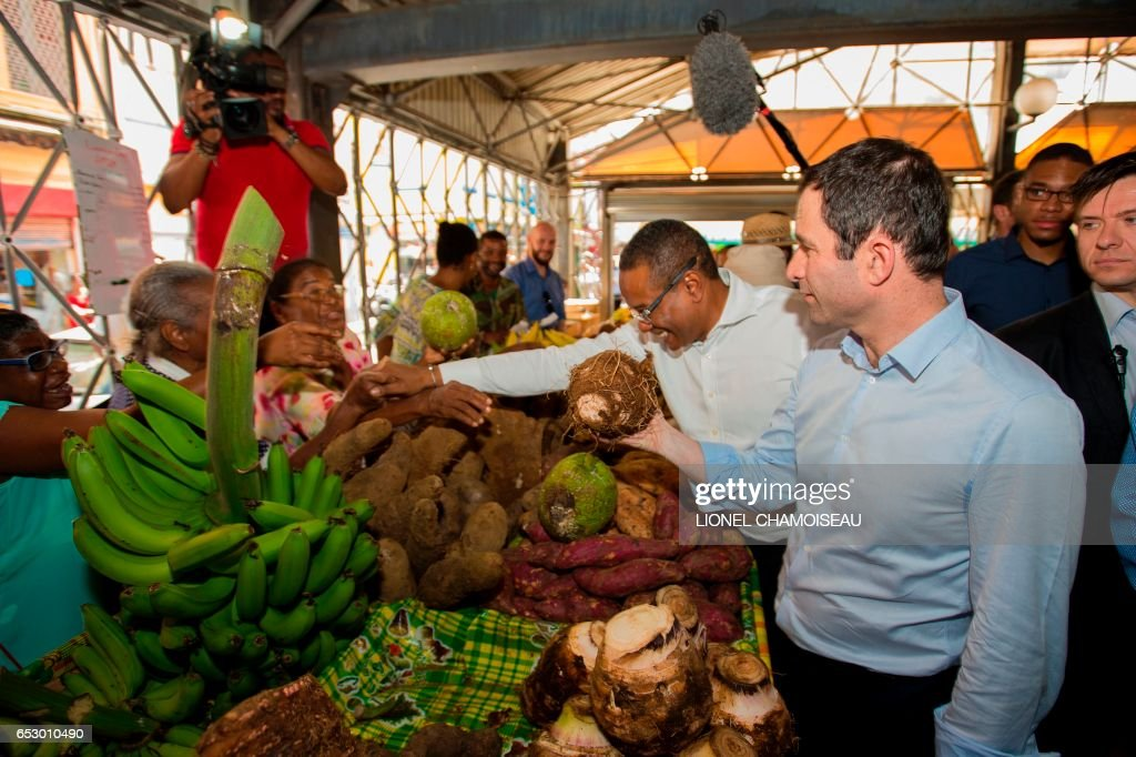 French presidential election candidate for the left-wing Socialist Party (PS) Benoit Hamon (3rd R), flanked by Mayor of Fort-de-France Didier Laguerre (C), holds fruit at the market of Fort-de-France on March 13, 2017, during a trip to the French overseas territory of Martinique. / AFP PHOTO / Lionel CHAMOISEAU