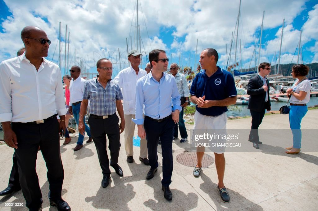French presidential election candidate for the left-wing Socialist Party (PS) Benoit Hamon (C) visits a dry dock in Le Marin on March 13, 2017, during a trip to the French overseas territory of Mar...